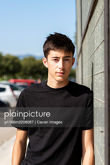 Young guy leaning on metallic fence,looking camera - p1166m2208087 by Cavan Images