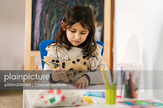 Cute girl doing homework while sitting at table - p300m2290489 by Ezequiel Giménez