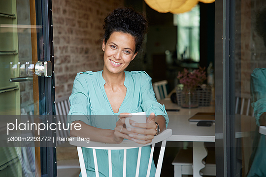 Smiling businesswoman holding coffee cup while sitting on chair - p300m2293772 by Rainer Berg