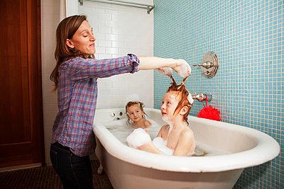 Mother bathing kids in bathtub - p1166m985113f by Cavan Images