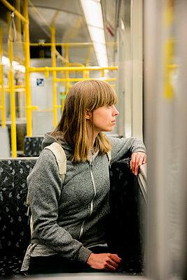 Junge Frau mit Rucksack sitzt in der U-Bahn  - schaut aus dem Fenster - p1212m1137017 von harry + lidy