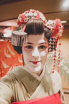 A woman dressed in the traditional geisha style wearing a kimono  - p1345m2055588 by Alexandra Kern