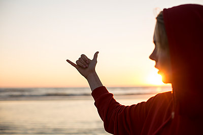 Young woman wearing red hooded jacket on the beach at sunset making hang loose gesture - p300m2029365 by Jean Schwarz