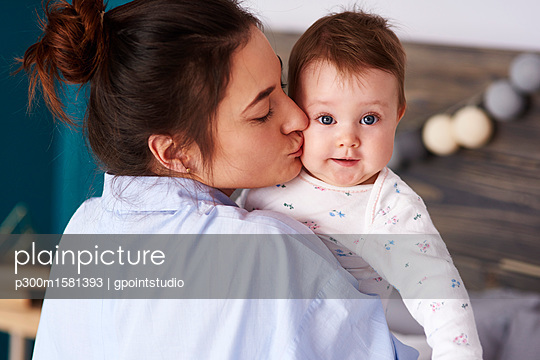 Mother carrying and kissing her baby at home - p300m1581393 by gpointstudio