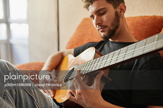 Man playing guitar on couch - p300m1586998 von Josep Rovirosa