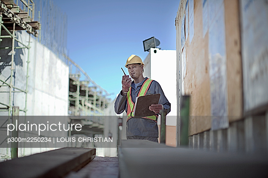 Male construction worker talking on walkie-talkie at construction site - p300m2250234 by LOUIS CHRISTIAN