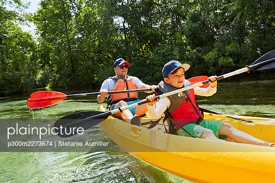 Boy with father in life jacket canoeing with oar in lake during picnic - p300m2273674 by Stefanie Aumiller