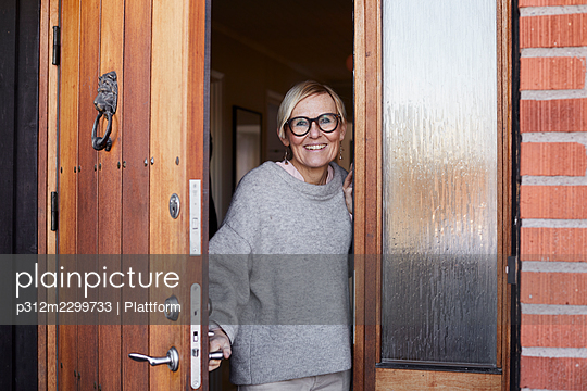 Smiling woman at front door - p312m2299733 by Plattform