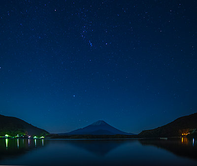 Starry sky over Mount Fuji on a clear night from lake Shoji, Yamanashi Prefecture, Japan - p1166m2157087 by Cavan Images