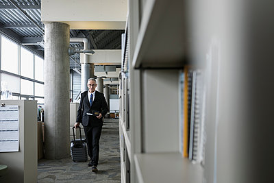 Mature businessman walking with suitcase in office corridor - p1192m1517122 by Hero Images