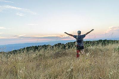 Spain, Catalonia, Man standing at Montserrat at sunset - p300m2012333 von VITTA GALLERY