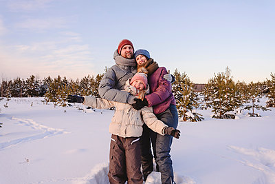 Happy family in warm clothing standing on snow against sky during winter - p300m2265144 by Ekaterina Yakunina