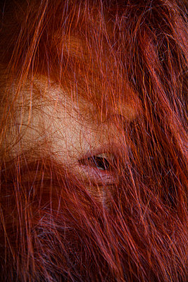 Rote Haarsträhnen vor dem Gesicht einer Frau - p427m2210804 von Ralf Mohr