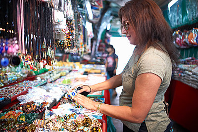 Woman looking at souvenirs on market stall, Bangkok, Krung Thep, Thailand, Asia - p429m1514091 by Peter Muller