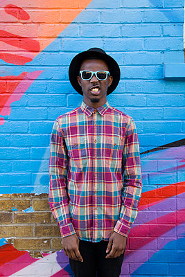 Black man wearing sunglasses near colorful wall - p555m1409904 by verity jane smith