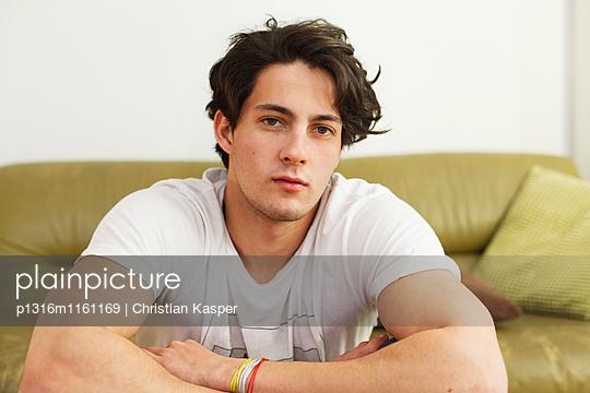 Junge Mann sitzt auf dem Sofa, Nachdenklich - p1316m1161169 von Christian Kasper