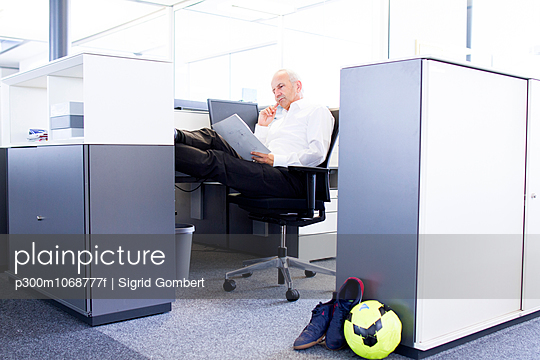 Businessman in office cubicle reading document