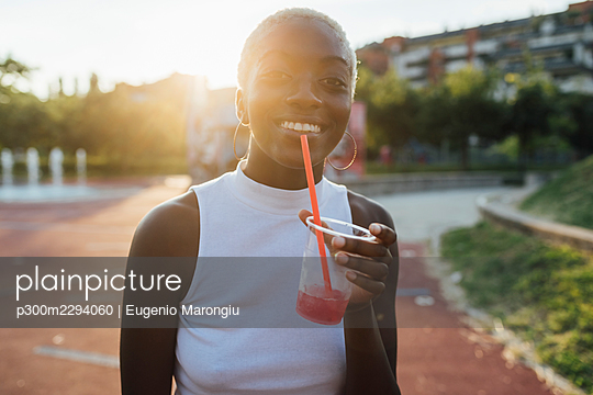 Smiling woman holding smoothie while standing at park - p300m2294060 by Eugenio Marongiu