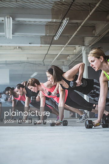Athletes doing push-ups with dumbbells on floor - p555m1411969 by John Fedele