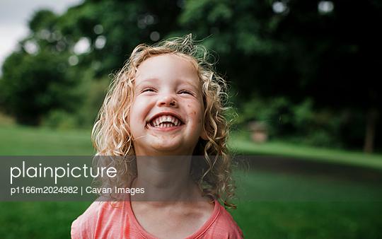 Cute cheerful girl looking away at park - p1166m2024982 by Cavan Images