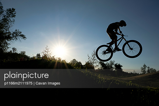 Side view of silhouette boy jumping while cycling against sky on field during sunset - p1166m2111975 by Cavan Images