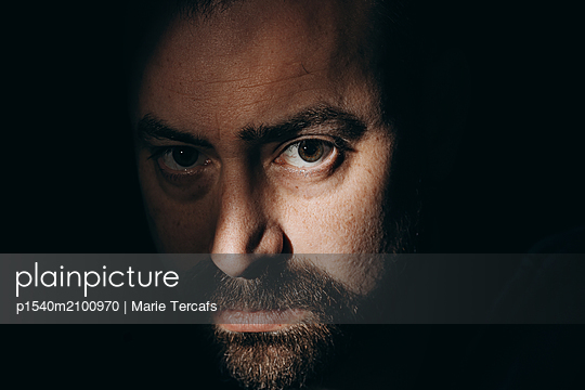 Close-up portrait of a bearded man in a dramatic light - p1540m2100970 by Marie Tercafs