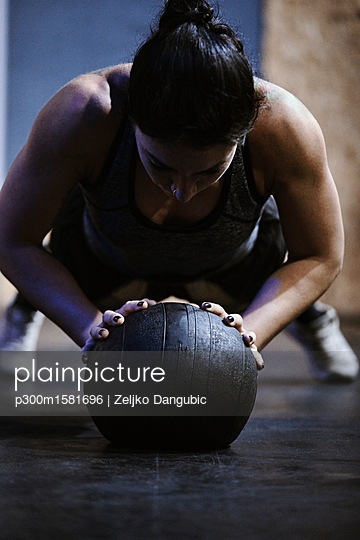 Woman doing push ups on ball in gym - p300m1581696 von Zeljko Dangubic
