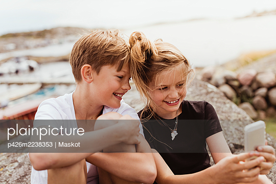 Smiling brother and sister taking selfie on smart phone at marina - p426m2238353 by Maskot