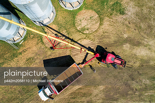 Aerial view looking straight down on a truck full of grain filling augers to large metal grain bins; Acme, Alberta, Canada - p442m2058110 by Michael Interisano