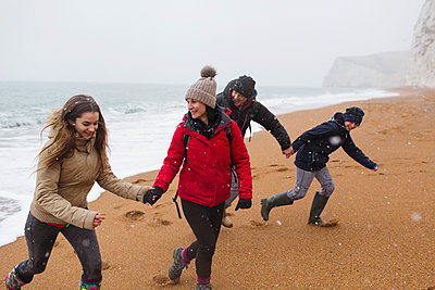 Playful family in warm clothing on snowy winter beach - p1023m2024279 by Sam Edwards