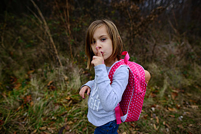 High angle portrait of girl with finger on lips standing on field - p1166m1486217 by Cavan Images