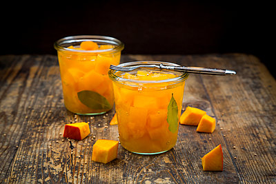 Two glasses of sweet-and-sour pickled pumpkin on dark wood - p300m1505783 by Larissa Veronesi