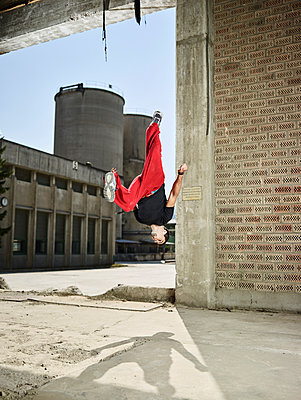Man jumping midair during freerunning exercise - p300m2012469 von Christian Vorhofer