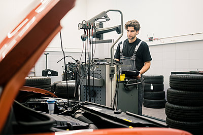 Car mechanic in a workshop using modern diagnostic equipment - p300m2166840 by Robijn Page