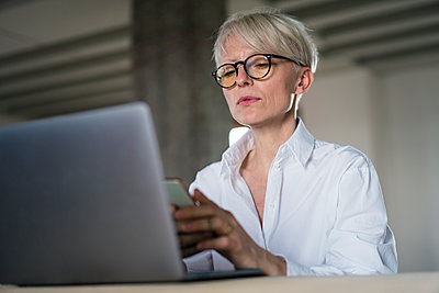 Businesswoman with laptop using smart phone while sitting at home office - p300m2267801 by Robijn Page