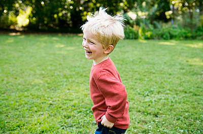 Happy boy laughing and running in grass - p301m2202378 by Tamara Lackey