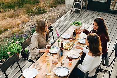 High angle view of female friends talking while enjoying meal at front yard - p426m2149269 by Maskot