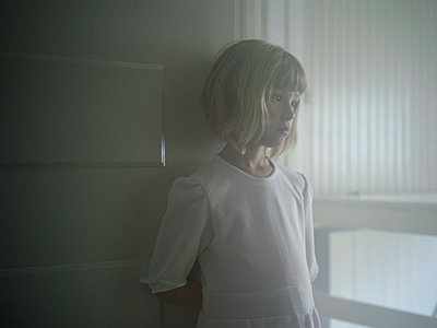 Sad girl leaning against door  - p945m1446198 by aurelia frey