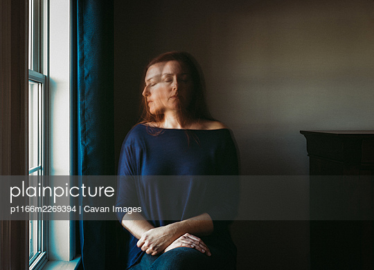 Woman with blurry face sitting alone in a dark room beside a window. - p1166m2269394 by Cavan Images