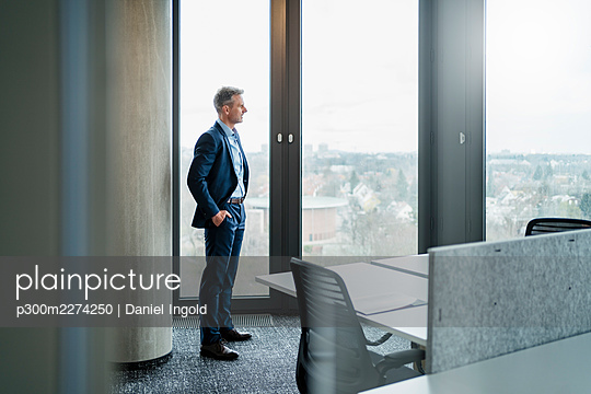 Mature businessman with hands in pockets looking through window in office - p300m2274250 by Daniel Ingold
