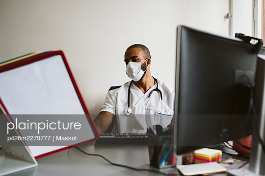 Male doctor wearing protective face mask reading medical files while sitting at desk - p426m2279777 by Maskot