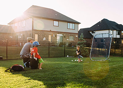 Family playing baseball at backyard on sunny day - p1166m1174177 by Cavan Images