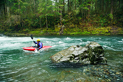 Side view of kayaker paddling through river in forest - p1166m1534050 by Cavan Images