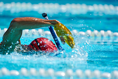 Close up of swimmer doing freestyle stroke at outdoor swimming pool - p1166m2095672 by Cavan Images