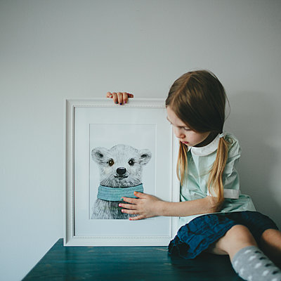Girl looking on a framed picture - p1414m1590580 by Dasha Pears