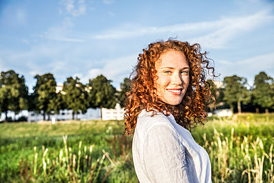Germany, Cologne, portrait of smiling young woman with curly red hair in nature - p300m2029200 by Jo Kirchherr