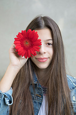 Portrait of smiling girl with flower head of red Gerbera - p300m2062281 von Petra Stockhausen