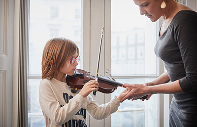 Teacher teaching boy playing violin during a lesson - p300m2189479 by Phillip Waterman