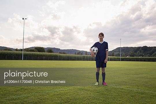 Junge mit Ball auf dem Fußballplatz - p1206m1170048 von Christian Brecheis