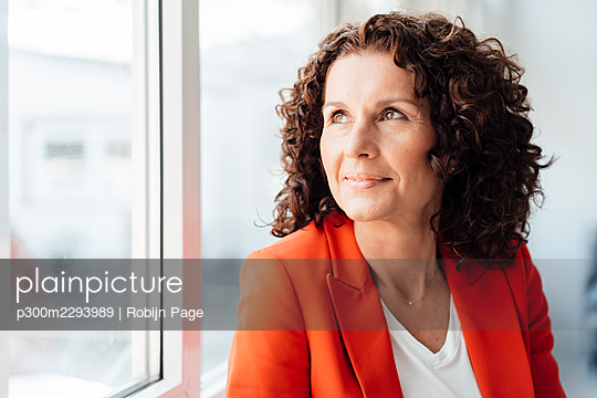 Curly haired businesswoman looking through window while contemplating - p300m2293989 by Robijn Page
